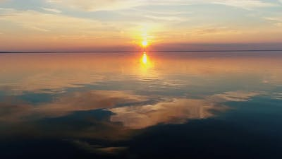 Fly Over Calm Water To Sunset