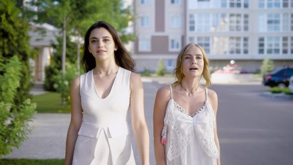 Thumbnail for Young Women Stroll Along the Street, Friends Talk To Each Other About Fashion, Life and Men