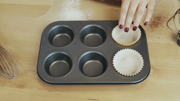 Thumbnail for View of Female Hand Putting the Paper Cups Into the Baking Tray Woman Cooking Cupcakes.