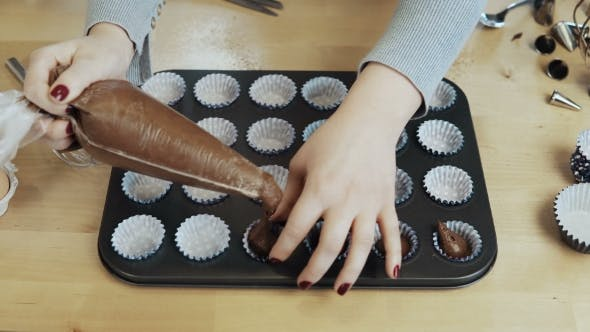Thumbnail for View of Female Hands Putting the Dough Into the Wrappers, Paper Cups for Cupcakes, Using Pastry Bag
