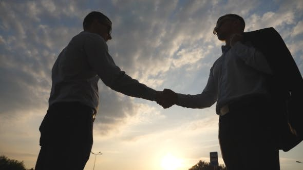 Thumbnail for Two Young Businessmen Greeting Each Other with Cloudy Sky at Background. Business Handshake Outdoor