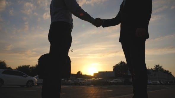Two Businessmen Greeting Each Other in Urban Environment at Sunset