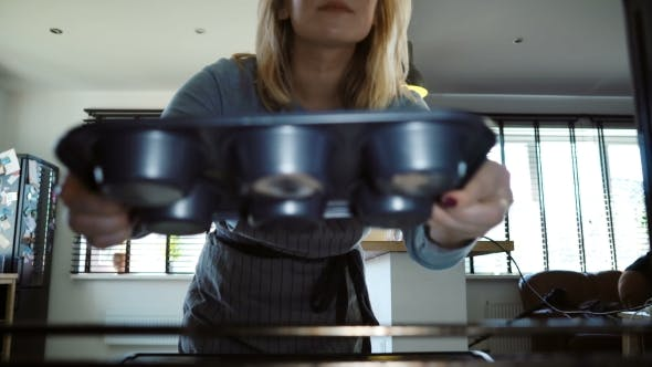 Thumbnail for Young Beautiful Woman Opens the Oven and Puts in the Baking Tray with Cupcakes Female
