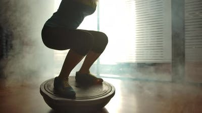 Sporty Girl Squatting on the Hemisphere in the Gym