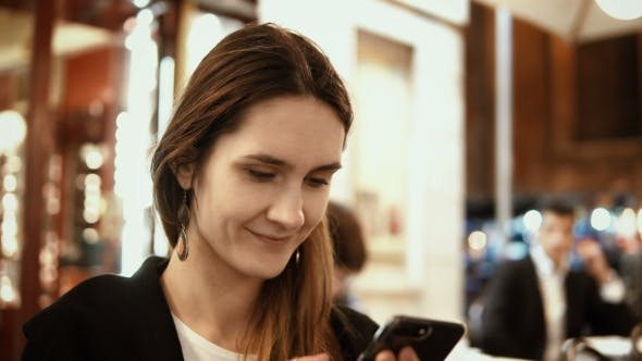 Thumbnail for Portrait of Young Beautiful Woman Sitting in the City Centre in the Evening and Using the Smartphone