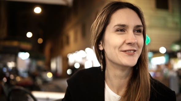 Thumbnail for Junge glückliche Frau im Gespräch mit Freund, sitzen im Café am Abend und trinken Kaffee in der