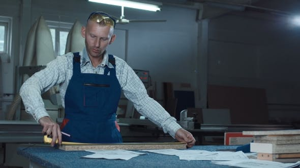 Thumbnail for Worker Measuring Plank in Shop