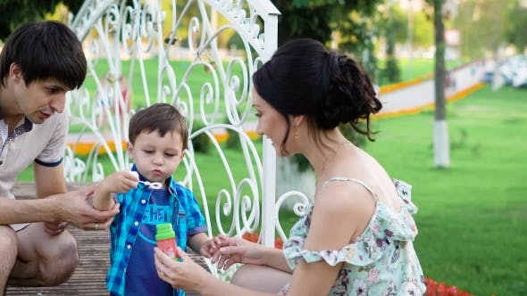 Thumbnail for Young Dark-haired Man and Woman Are Teaching Their Little Son To Blow Bubbles in Park in Summer Day
