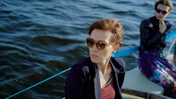 Thumbnail for Serious and Thoughtful Dark-haired Women Are Wearing Sunglasses Are Sitting on a Board of Boat