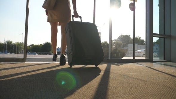 Thumbnail for Business Lady Walking From the Airport with Her Luggage. Woman in Heels Going Through Glass Door
