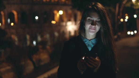 Thumbnail for Young Happy Woman Walking in Park Near the Colosseum in Rome, Italy and Using the Smartphone in the