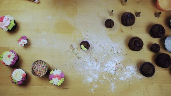Thumbnail for Top View of Chocolate Cupcakes on the Table. Young Woman Decorating Muffins with Colored Cream From