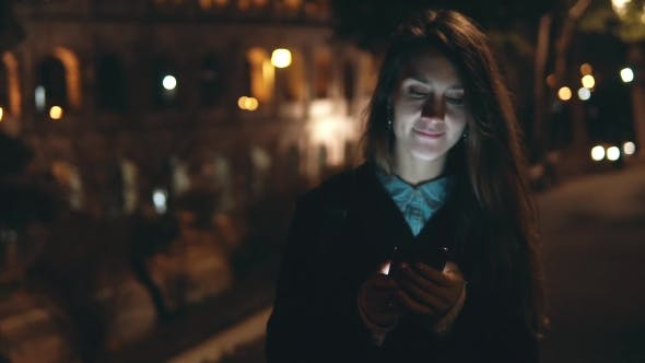Thumbnail for Young Brunette Woman Walking in the Evening Near the Colosseum in Rome, Italy and Using Smartphone