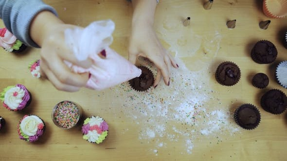 Thumbnail for Top View of Young Female Hands Decorating the Chocolate Cupcake or Muffin with Cream, Using Pastry