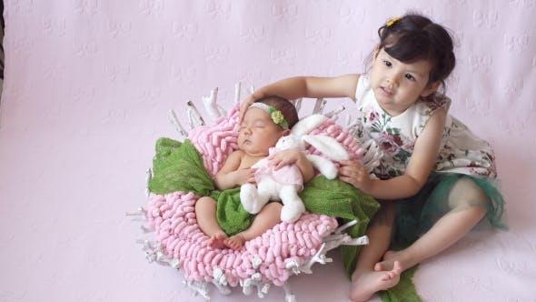 Thumbnail for Little Girl Looks at Her Baby Sister.
