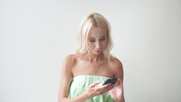 Thumbnail for Young Attractive Girl Uses a Smartphone in Spa Salon