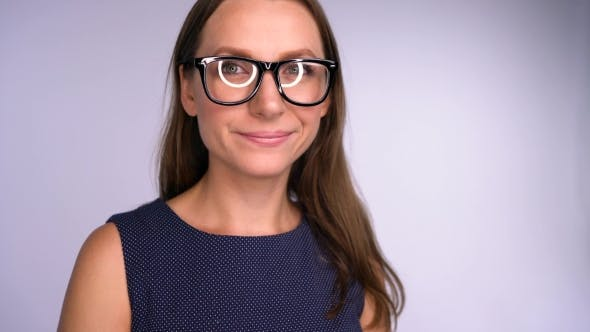 Young Business Woman in Glasses Looking at Camera Happy. Round Glare Is Reflected in the Glasses