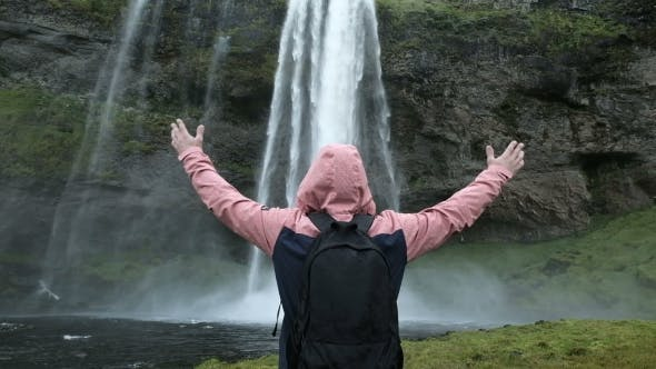 Thumbnail for Tourist Man in a Red Jacket Stands and Looks at a Stream of Falling Water. Beauty in Nature
