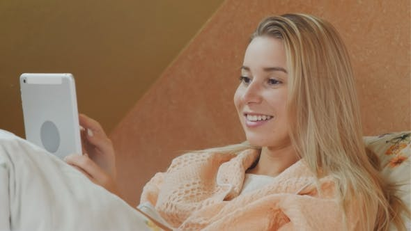 Thumbnail for Smiling Woman Using Digital Tablet While Lying in Hospital Bed
