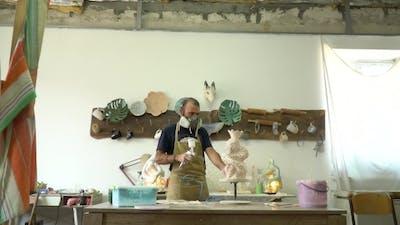 Man Painting a Sculpture