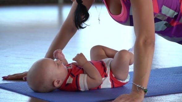 Thumbnail for Schießen als Mutter während Push-ups auf einer Matte für Yoga Küsse ein Kind