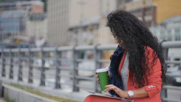 Cover Image for Fashionable Curly Lady Drinks Coffee and Work on Tablet at Urban Road Background