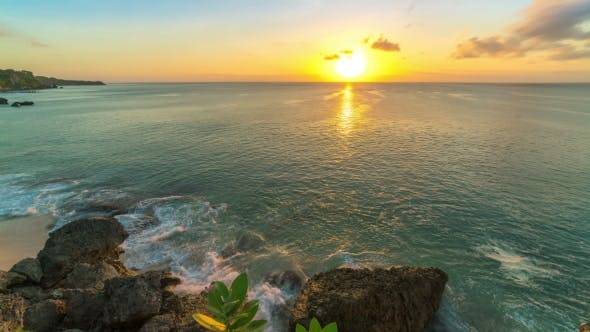 Thumbnail for of Sunset on the Beach of the Island of Bali in Indonesia, at the Bottom Waves Break Against the