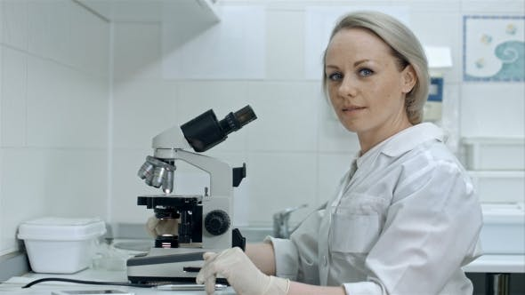 Thumbnail for Pretty Female with Microscope Looking at Camera in Laboratory