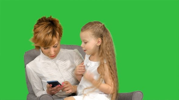 Thumbnail for Young Woman-mother and Child Look in Phone on a Green Screen