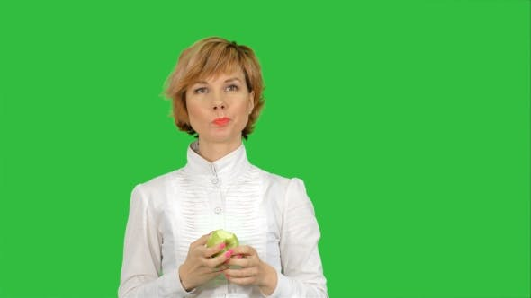 Thumbnail for Portrait of Young Woman Eating Green Apple on a Green Screen