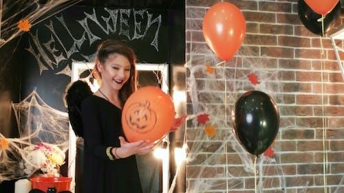Halloween-Feier, junge Hexe spielt Ballon mit Kürbis, Teenager-Mädchen mit gruseligem Kostüm