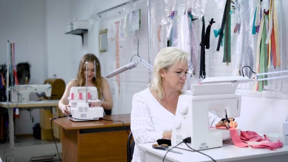 Thumbnail for Two Women Working on Clothing Manufacture. Woman in White Suit Sitting in the Foreground and Sewing