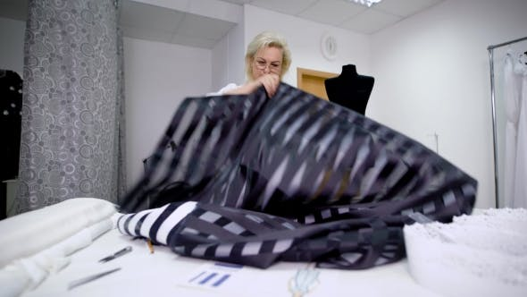 Thumbnail for Professional Couturier Is Working in Sewing Workshop Holding Black Cloth and Making Measurements
