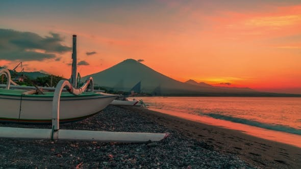 Cover Image for Sunset Overlooking the Agung Volcano in the Background of a Fishing Boat on the Beach of Jemeluk Bay