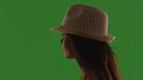 Silhouette of attractive young woman wearing fedora standing on green screen
