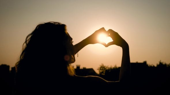 Thumbnail for View of Adorable Woman Silhouette Holding Sun in the Field with a Warm and Vague Background
