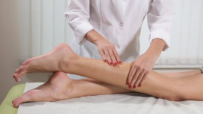Massage in a Beauty Salon. Massage the Feet of a Beautiful Girl. Hands  of a Massage Therapist.