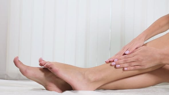 Young Woman Smearing Cream on Her Leg