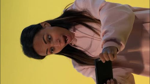 Pleasant-looking Black Girl Playing Games on Smartphone on Yellow Background.