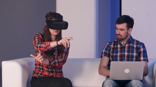 Cover Image for Smiling Girl in Virtual Reality Glasses Describing Something to a Man Sitting Next to Her