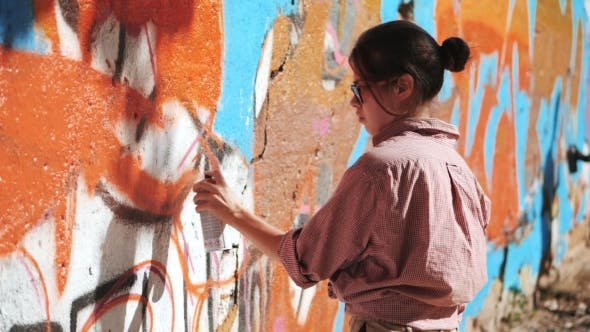 Thumbnail for Beautiful Young Girl Making a Colorful Graffiti with Aerosol Spray on Urban Street Wall. Cinematic