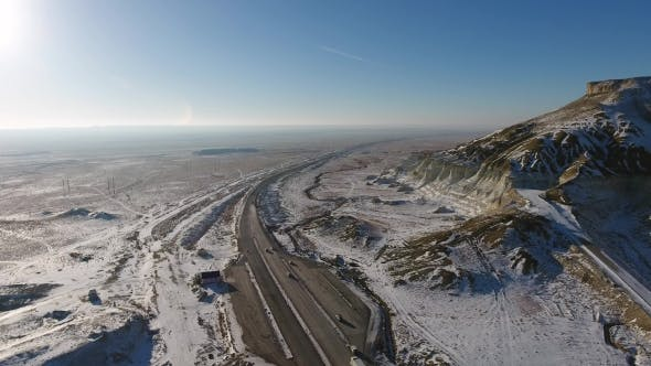 Thumbnail for Aerial View of Trucks and Suvs Moving Along the Highway in the Desert in Winter. Western Kazakhstan