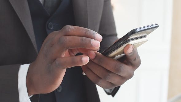 Thumbnail for Afro-american Businessman Reading Emails on His Smartphone and Texting Answers.