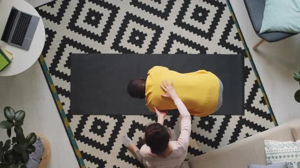 Black Man Practicing Yoga with Assistance of Wife
