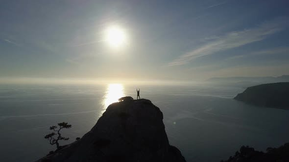 Thumbnail for Aerial Silhouette of Young Woman Standing on the Top of a Mountain Facing the Sea