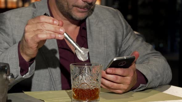 Thumbnail for Mature Man Using Smartphone While Adding Ice Cubes To His Whiskey