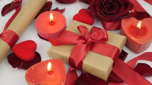 Decorated romantic background with burning candles, roses and presents gift boxes. Valentine's Day