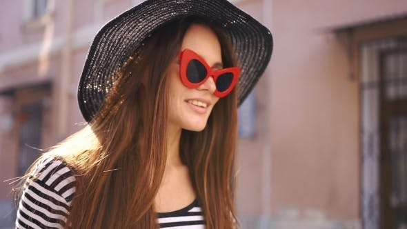 Thumbnail for Woman in Black Hat and Red Sunglasses Smiles Whirling on the Street