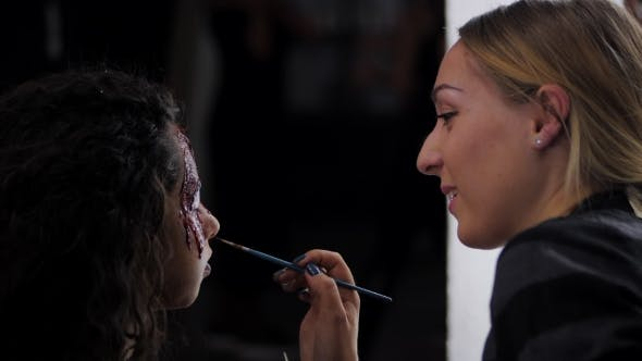 Make-up Artist Make the Girl Halloween Make Upin studio.Halloween Face art.Woman Applies on