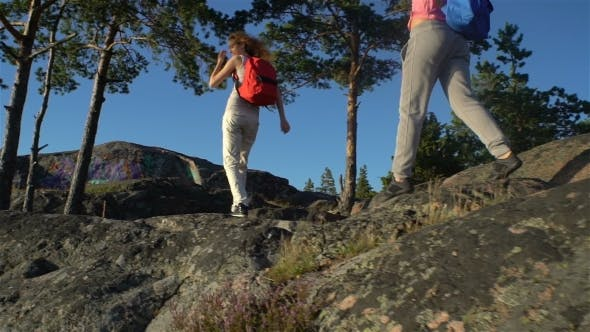 Thumbnail for Two Active Young Women Help Each Other To Climb a High Rock